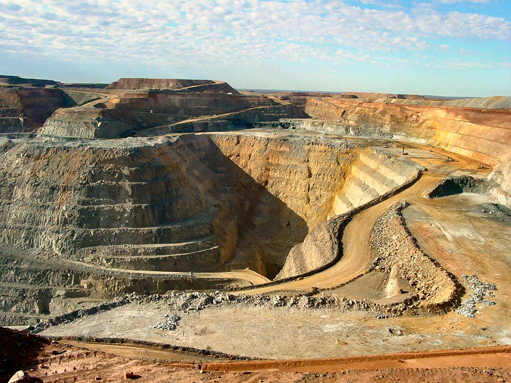 A deep opencut mine in which some roads can be seen, the dirt is a rusty colour