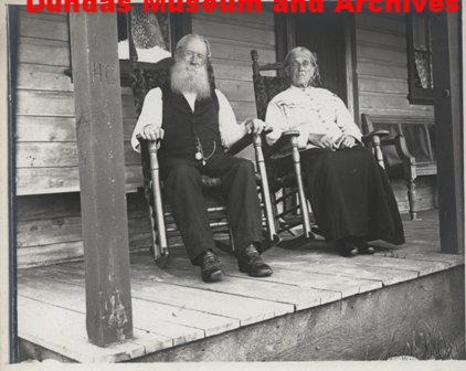 Two Old People Sitting On A Porch In Rocking Chairs The Woman Is Long Skirt And Light Blouse Man Dark Pants White Shirt With