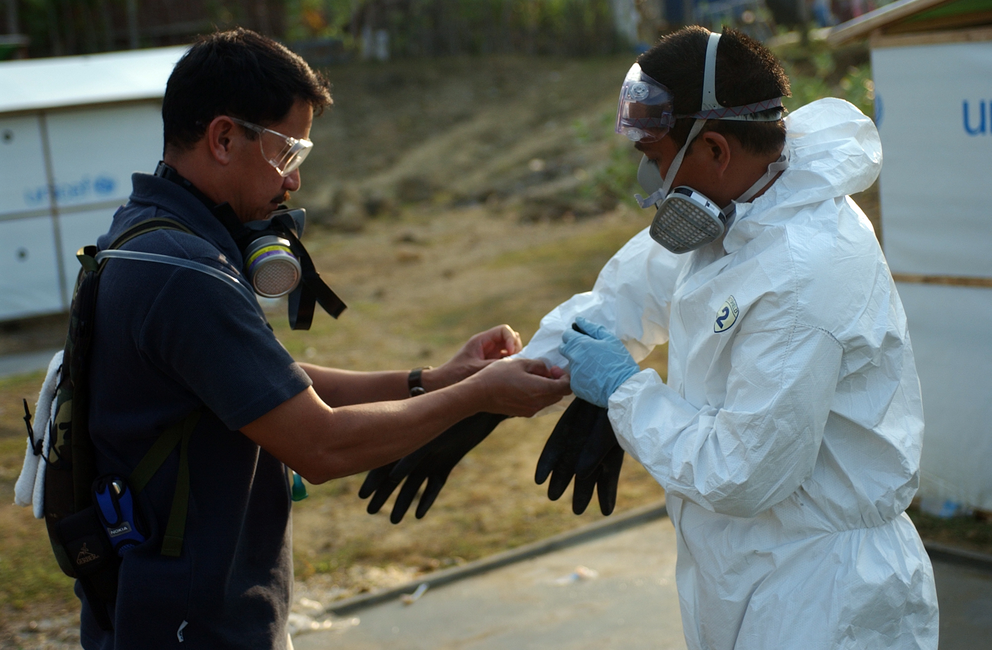 US Navy 050309-N-8796S-031 Chief Hospital Corpsman Alberto Redublo, left, helps Hospital Corpsman 2nd Class Richard Cabatit as he dons his personal protective equipment for spraying pesticides.jpg