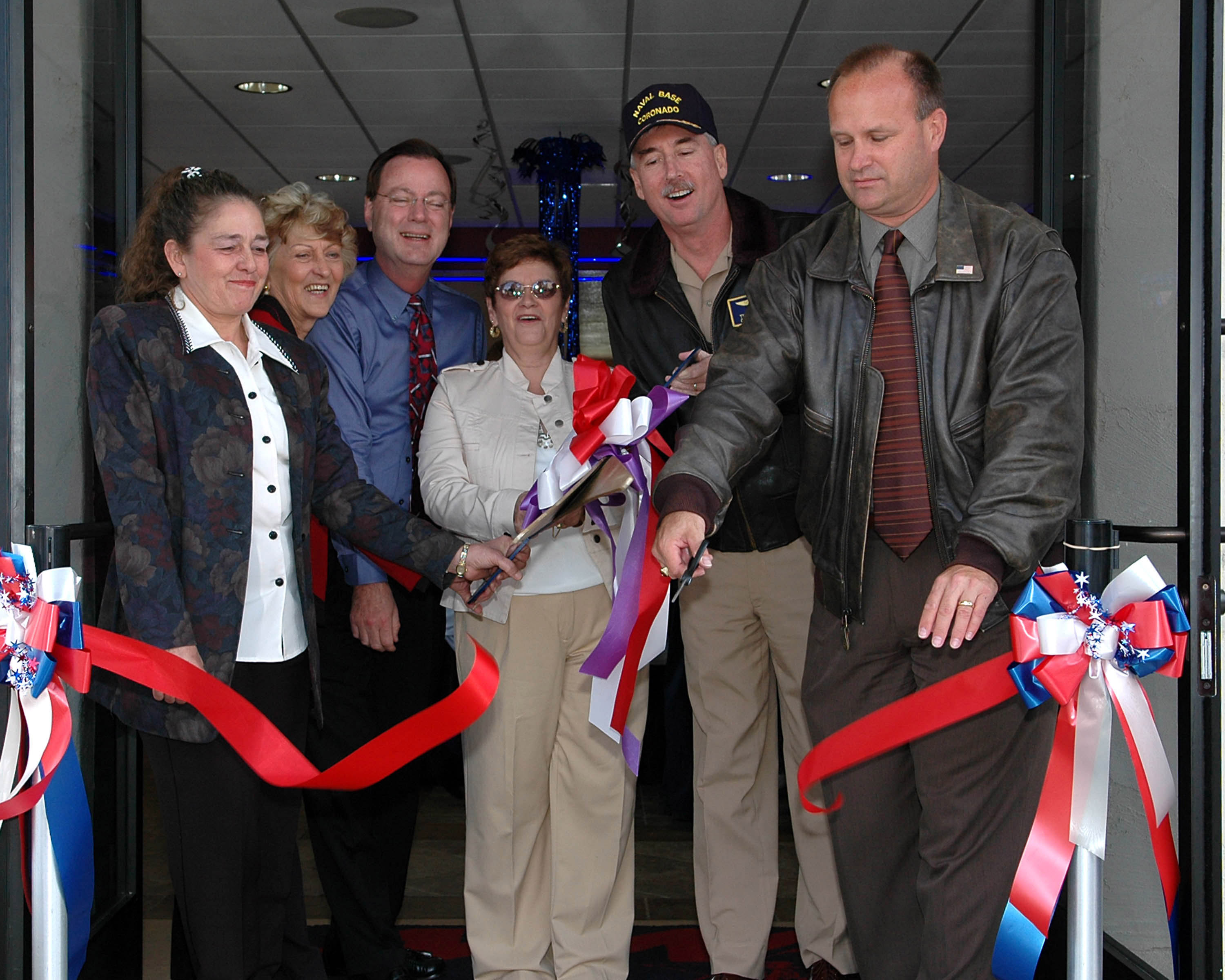representatives reopen the doors on a newly renovated pizza parlor at a ribbon cutting ceremony following a two-month renovation project funded by M.jpg English: