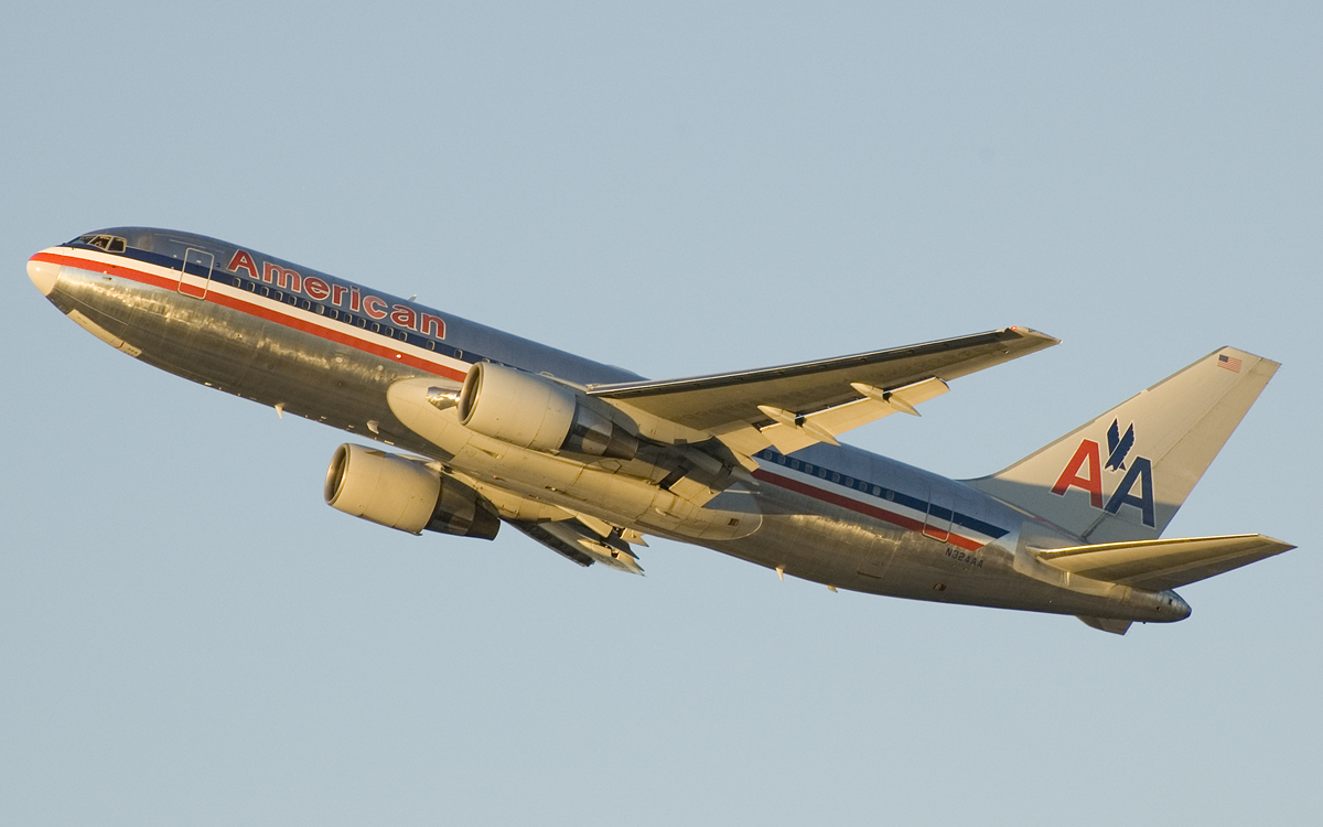 "Sideview of 767 on climbout against a pale blue sky. A blue, white and red cheat-line runs the full length of the fuselage, above which says ""American"". The vertical tail sports two ""A""s, between which is a simplified eagle."