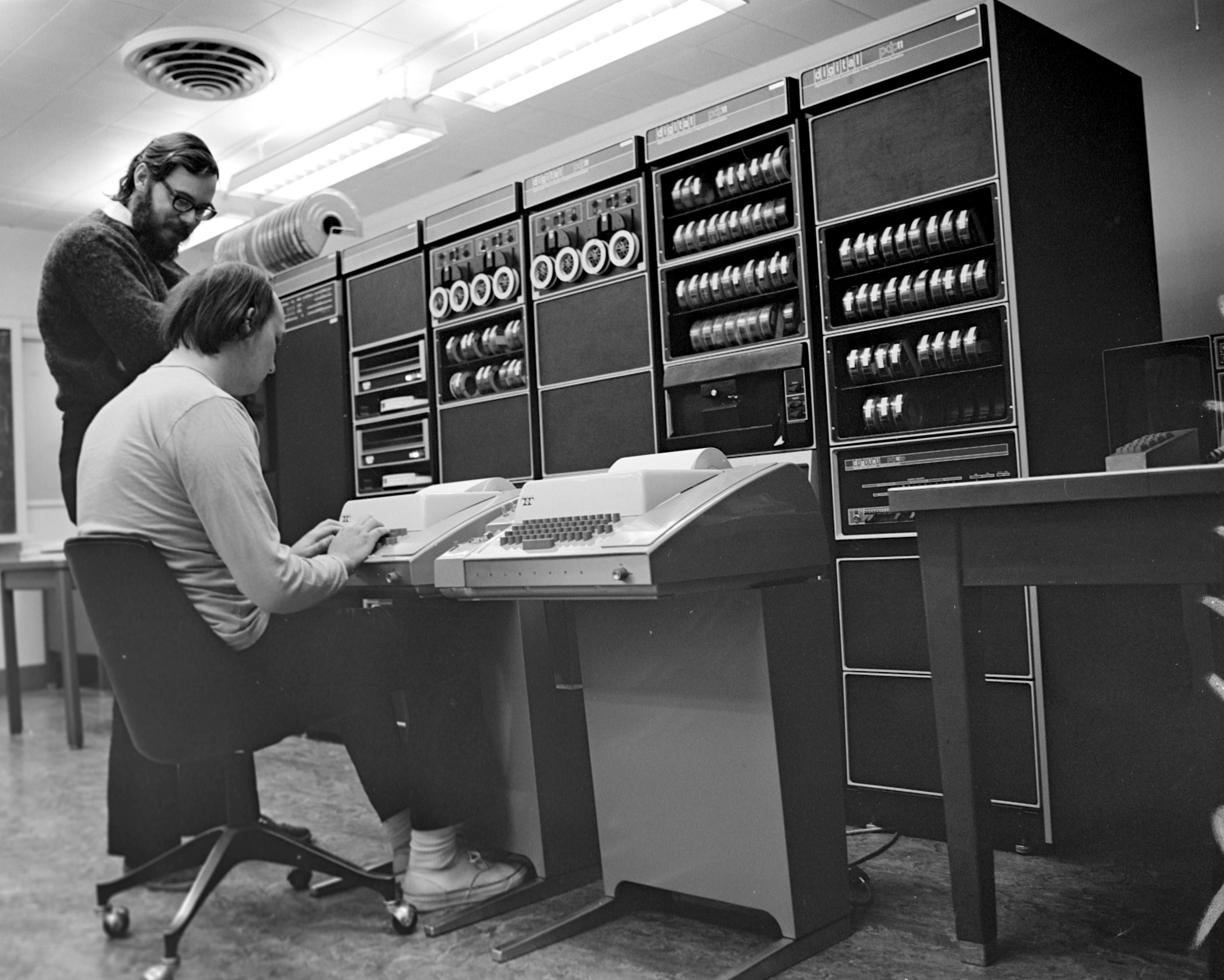 Ken Thompson sitting and Dennis Ritchie at PDP-11