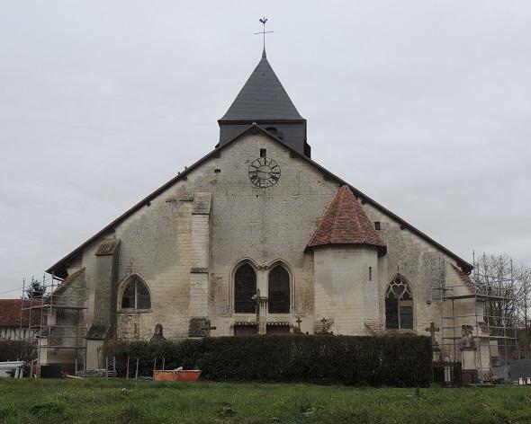 Église Saint-Parres, vue orientale, sans chevet, mais avec une tour hexagonale plus petite que le toit de l'église et de jolies arches sculptées; pelouse devant et maisons du bourg en arrière plan