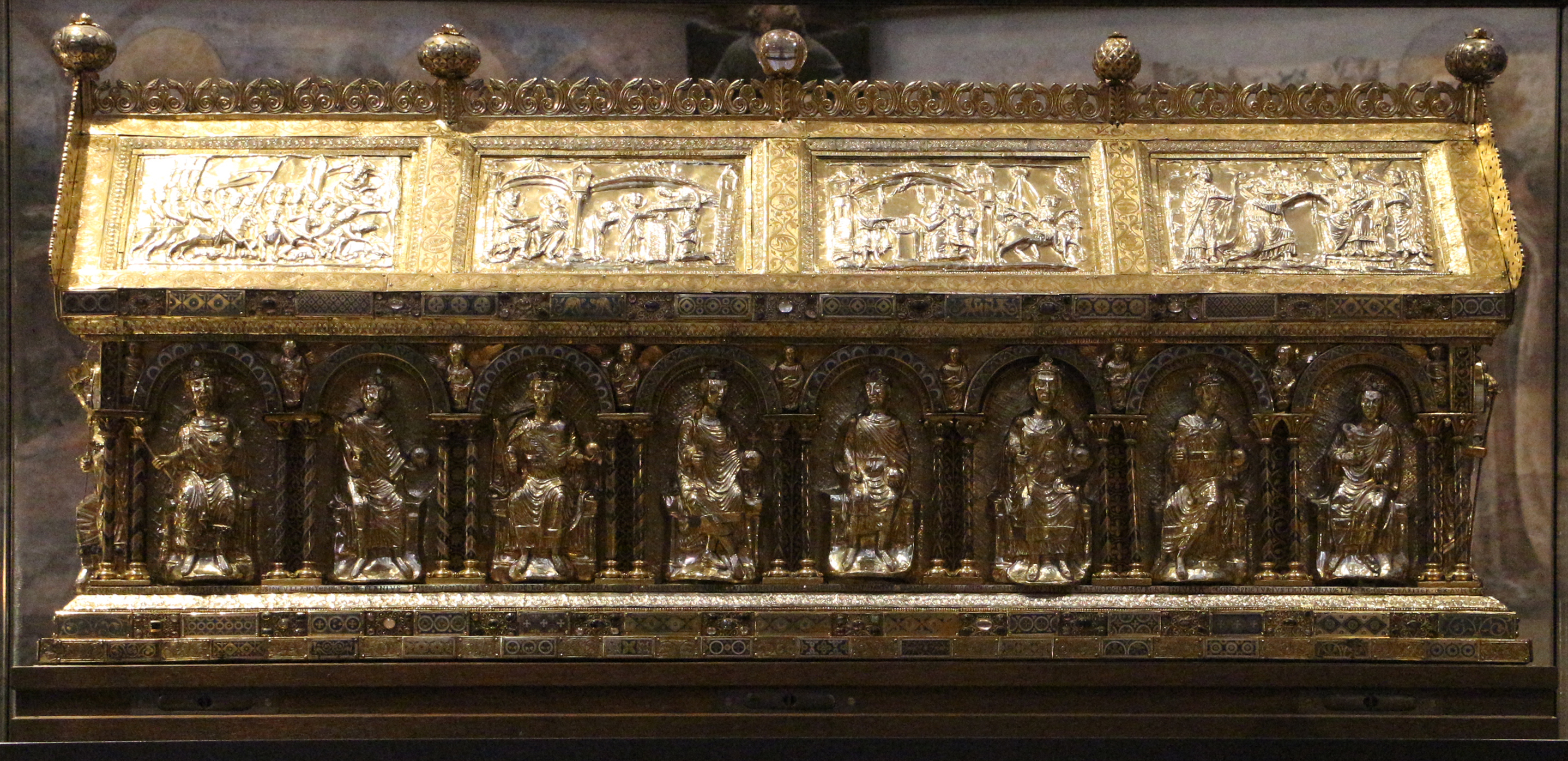 long gilt shrine, with panels depicting seated churchmen