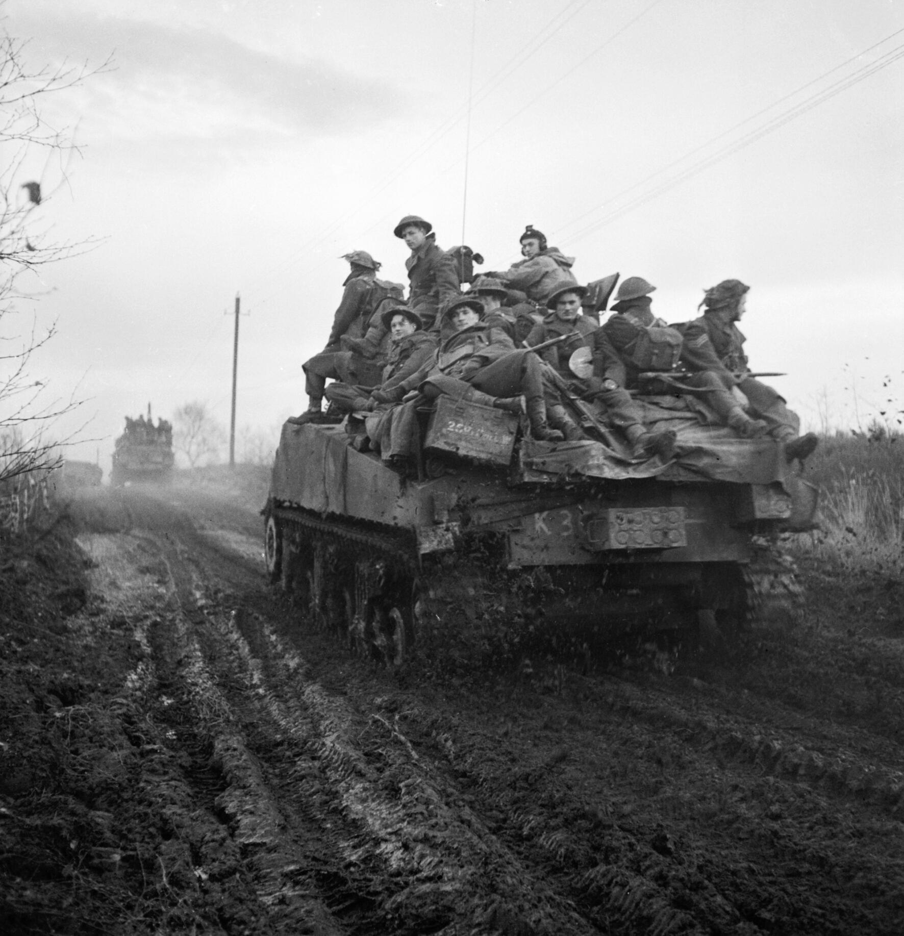Infantrymen on a Sherman tank