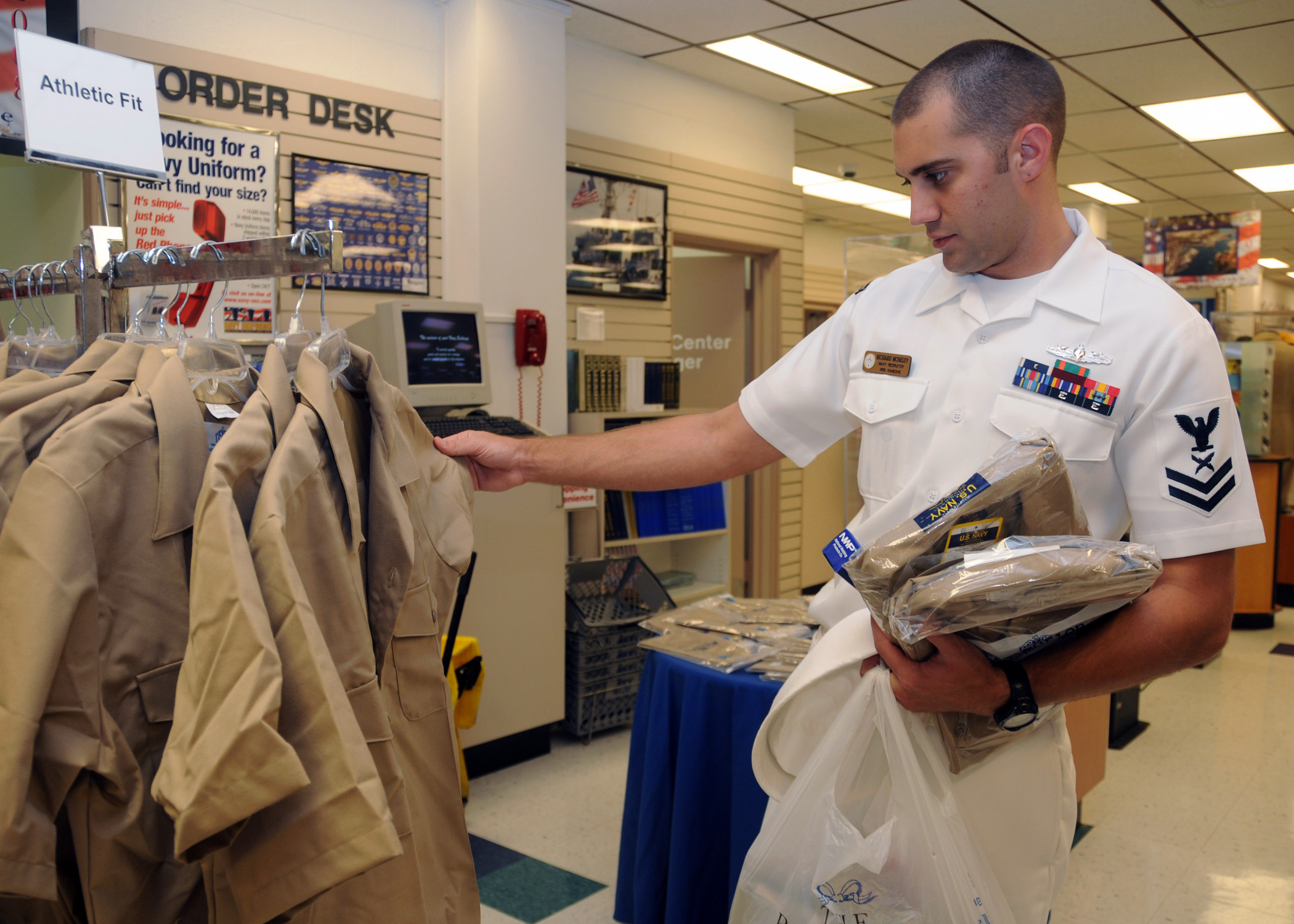 ... shops for the new service uniform at the Navy Exchange Uniform Shop