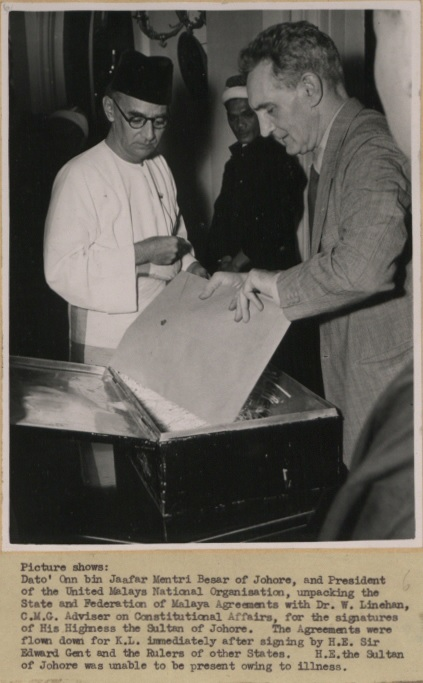 Dato' Onn bin Jaafar Mentri Besar of Johor, and President of the United Malays National Organisation, unpacking the State and Federation of Malaya Agreements with Dr. W. Linehan, C.M.G. Adviser on Constitutional Affairs, for the signatures of His Highness the Sultan of Johor, 1948 CO 1069-504-06 (7893277526).jpg