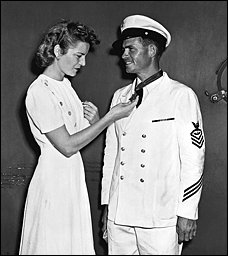 A woman stands next to a man dressed in chief petty officer dress whites admiring a medal of honor the man is wearing