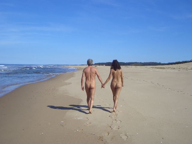 Naked couple walking along the beach (Chihuahua, Uruguay).jpg