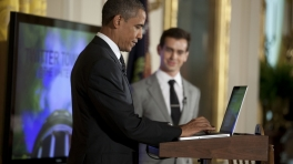 Barack Obama in a blue suit typing on computer at a podium while a white man in a light grey suit looks on