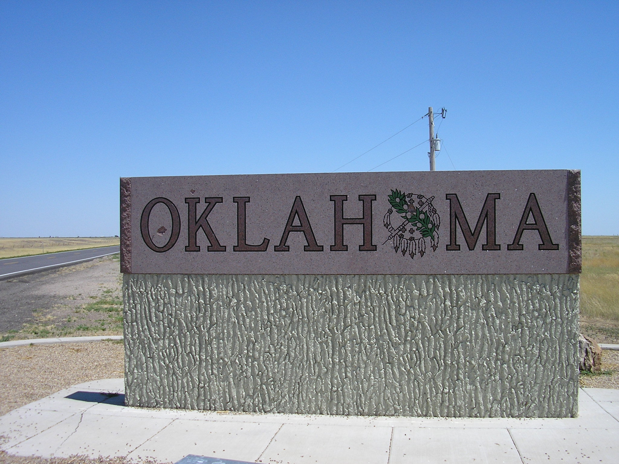 The state's high plains stretch behind a greeting sign in the Oklahoma Panhandle.