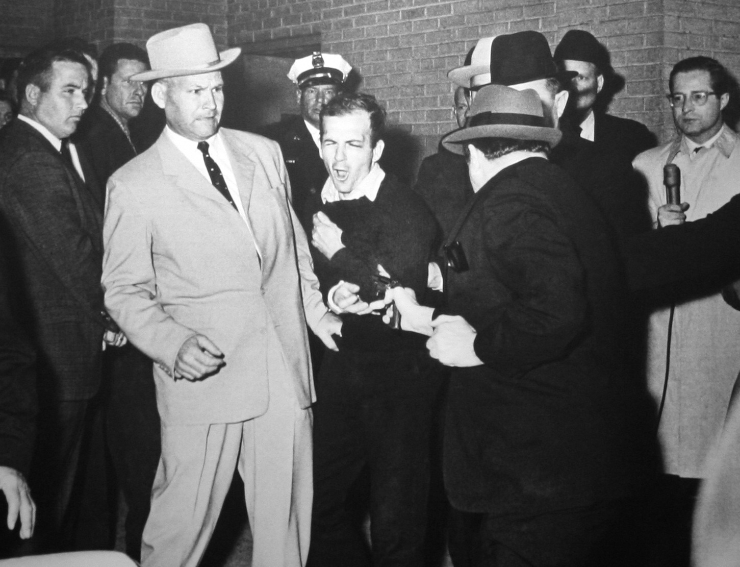 Ruby shooting Oswald, who is being escorted by Dallas police. Detective Jim Leavelle is wearing the tan suit.