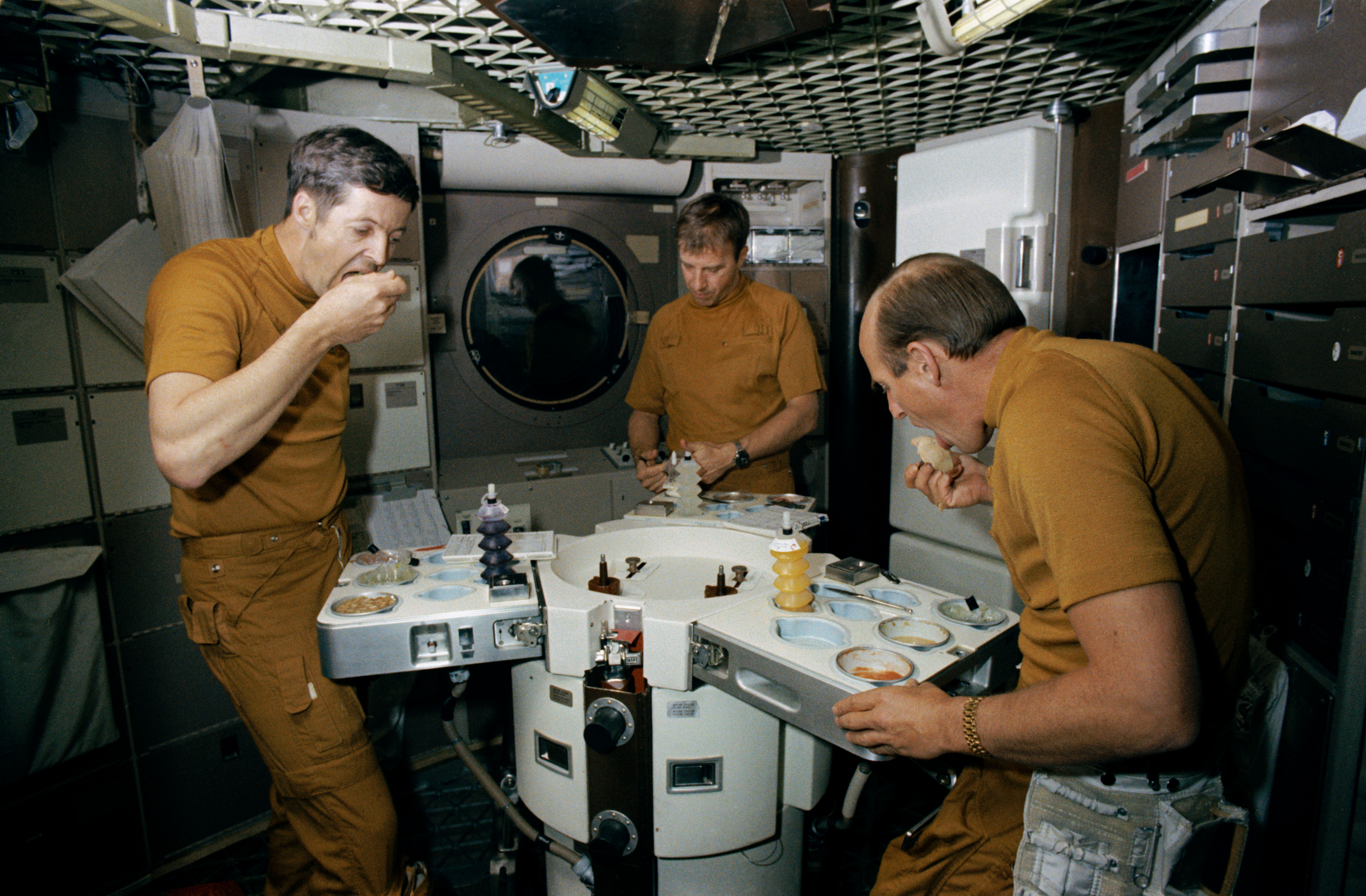 Skylab 2 astronauts eat space food in wardroom of Skylab trainer | Astronaut Chow: Space Food over the Years