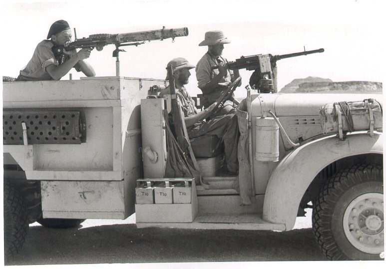 posed picture of three men one sitting in the drivers seat and the other two aiming machine guns