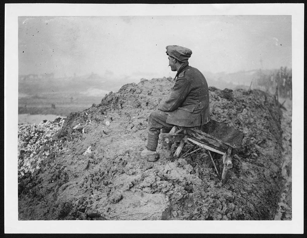 This rather evocative photograph shows a single British soldier sitting on a wheelbarrow, apparently lost in his thoughts, while horse transports move along the road behind him. For the ordinary soldier, moments of solitude would have been few and far between.The sentimentality of the original caption and the anonymity of the profiled head, suggest that this photograph may have been intended for consumption on the Home Front. In reality, as many first-hand accounts show, home often seemed an unreal dream to men at the Front. [Original reads: 'Thoughts of home.'] http://digital.nls.uk/74549476