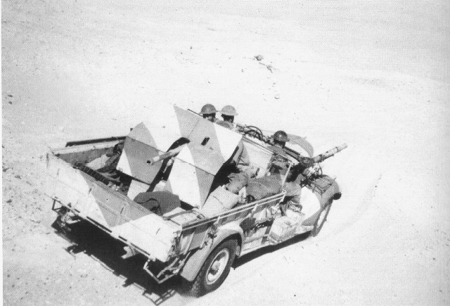 four wheeled truck mounting a large artillery piece at the rear and a Lewis gun at the front. The three-man crew can also be seen