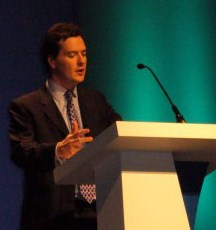 Osborne speaking at a podium, gesturing with his hands.