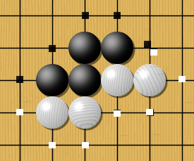 One black chain and two white chains, with their liberties marked with dots. Liberties are shared among all stones of a chain and can be counted. Here the black group has 5 liberties, while the two white chains have 4 liberties each.