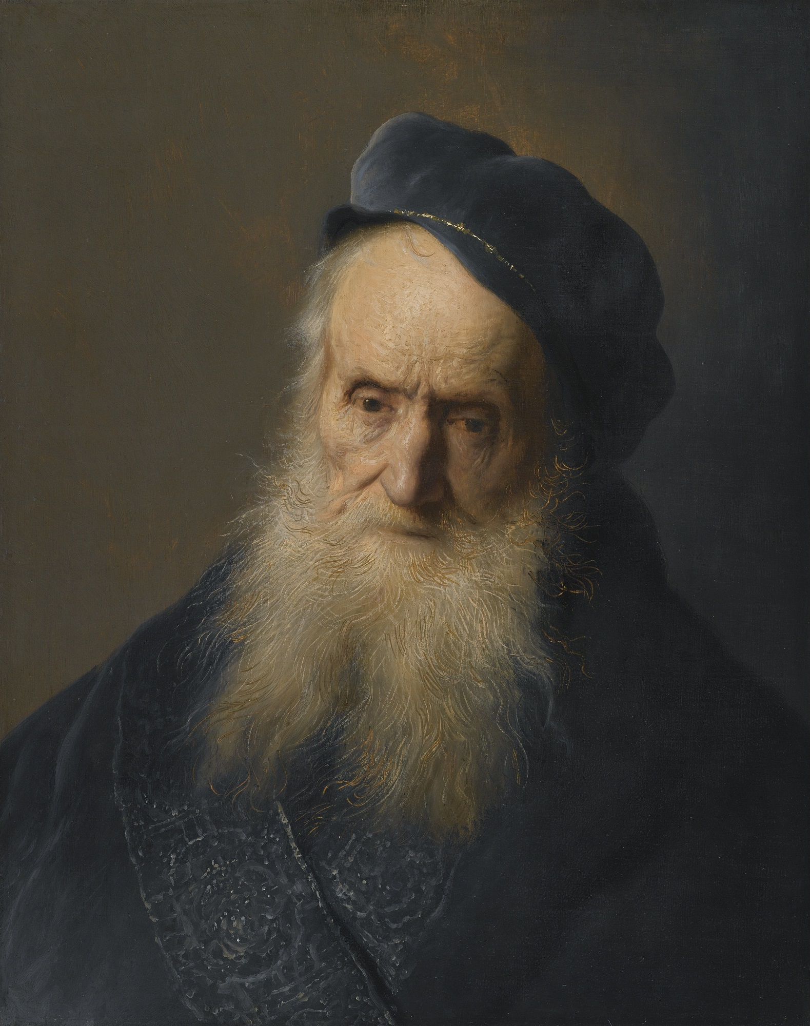 A serious elderly man, with a long white beard, wearing a blue soft cap and gown.