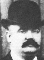 Black and white photograph of a man wearing a bowler hat. He also has a thick black moustache
