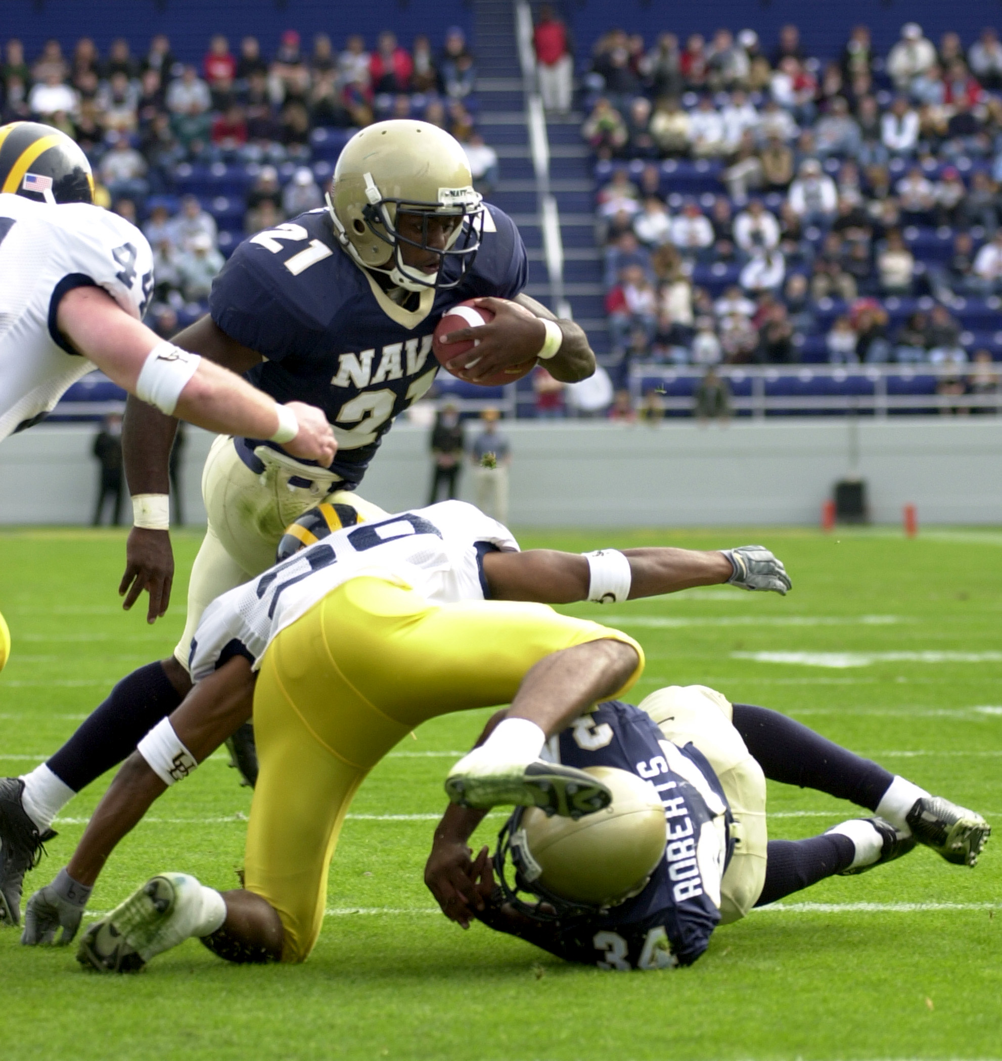 031025-N-9693M-002 Navy slot back Tony Lane passes Delaware defensive back Ryan Trask during the U.S. Naval Academy's homecoming game against Univeristy of
