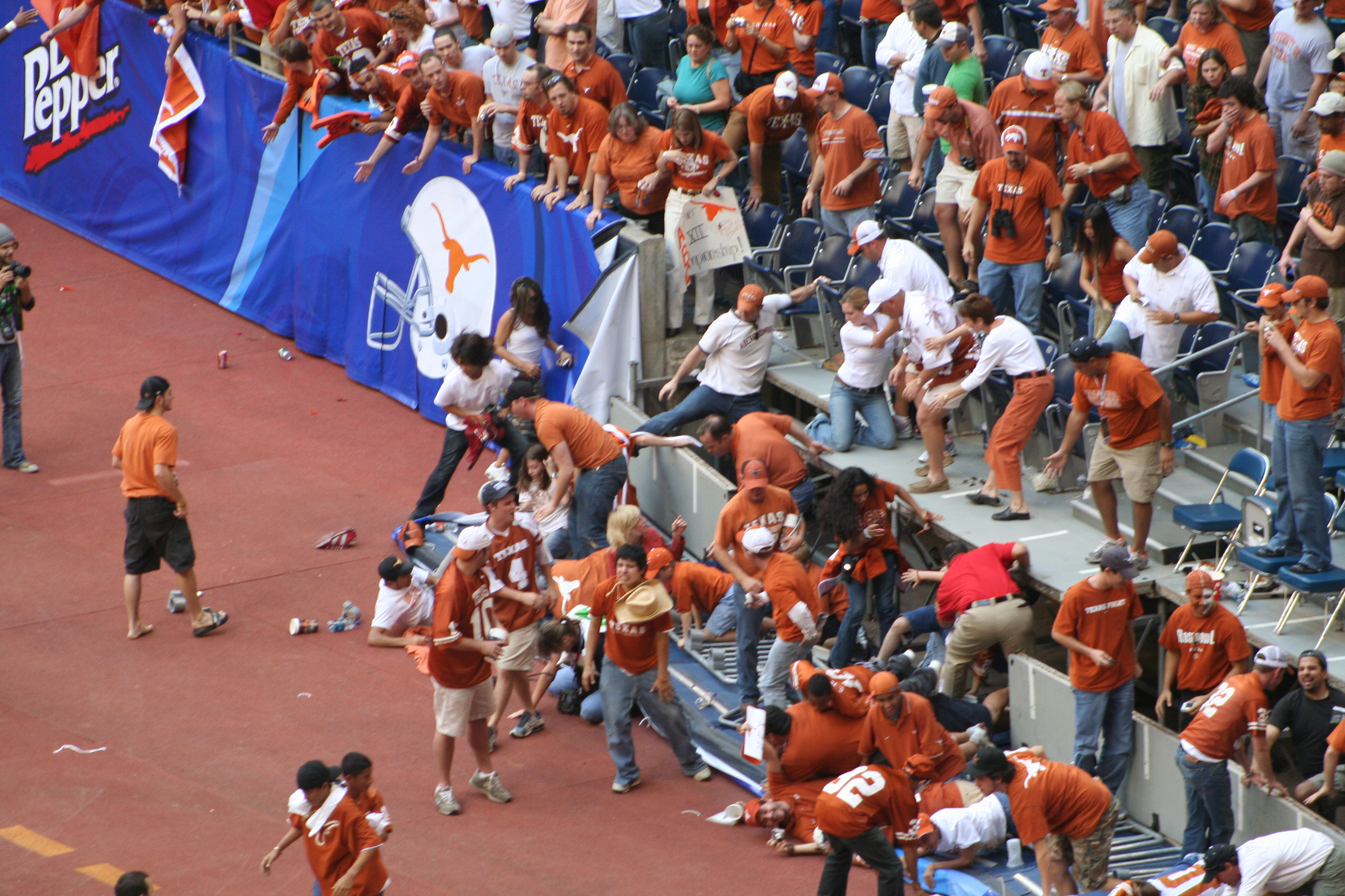 A railing accident at a college football game, spilling fans onto the side lines