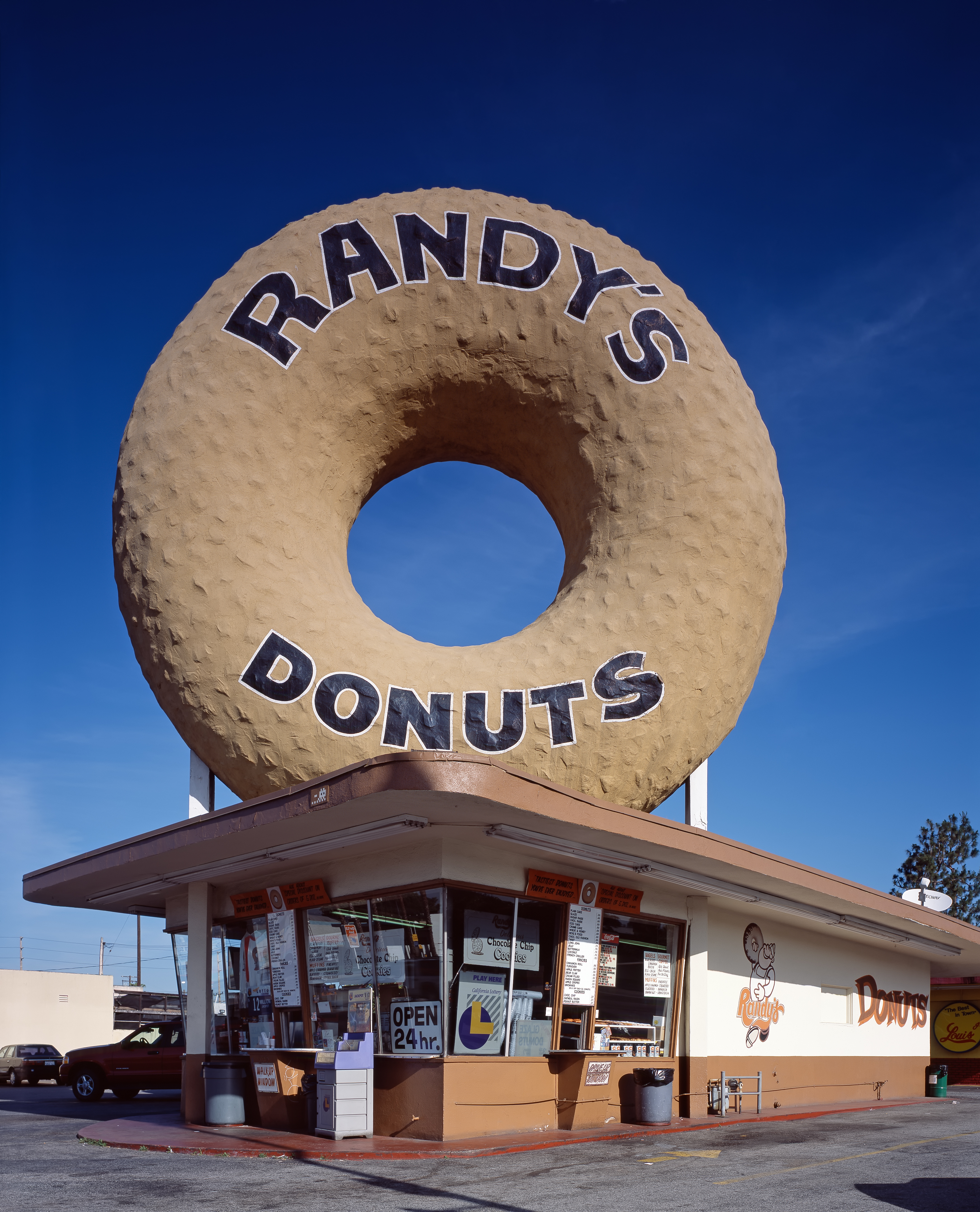 A picture of a Randy s Donuts location with donut sculpture on the roof