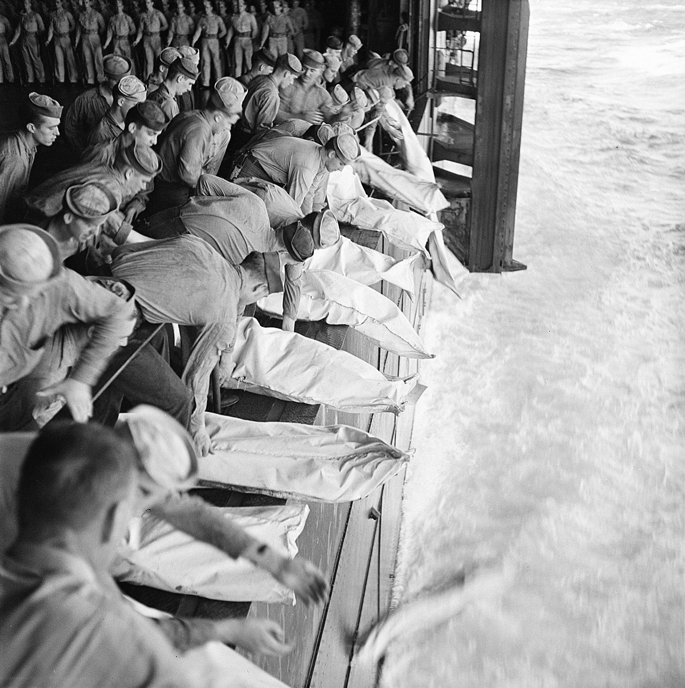 Sailors preparing to slide shrouded bodies over the side