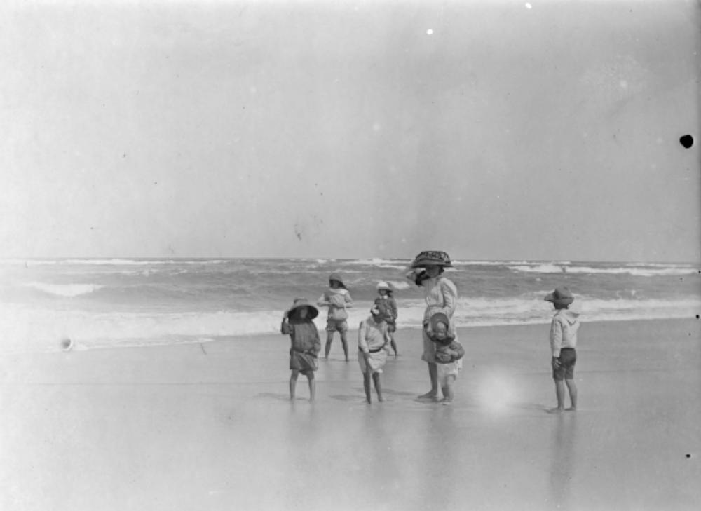 FileStateLibQld 2 199447 On The Beach A Girl Wearing A Large Hat Stands With Six Younger