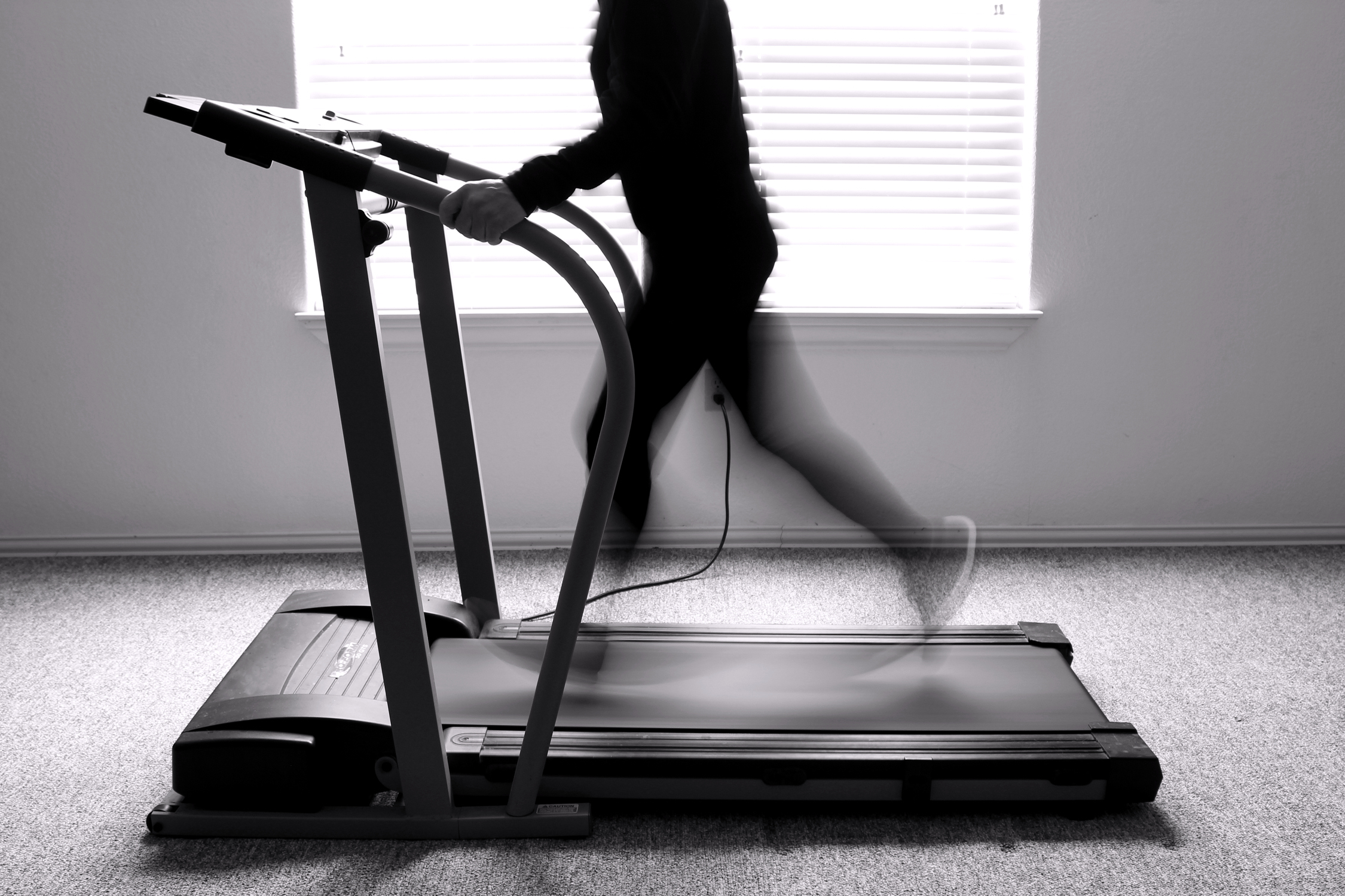 Man exercising on a treadmill (black and white).