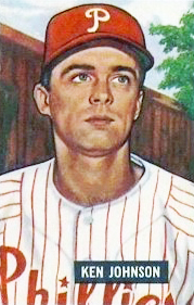 "A baseball card image of a man in a white baseball jersey pinstriped with red and a red baseball cap with a white ""P"" on the front"