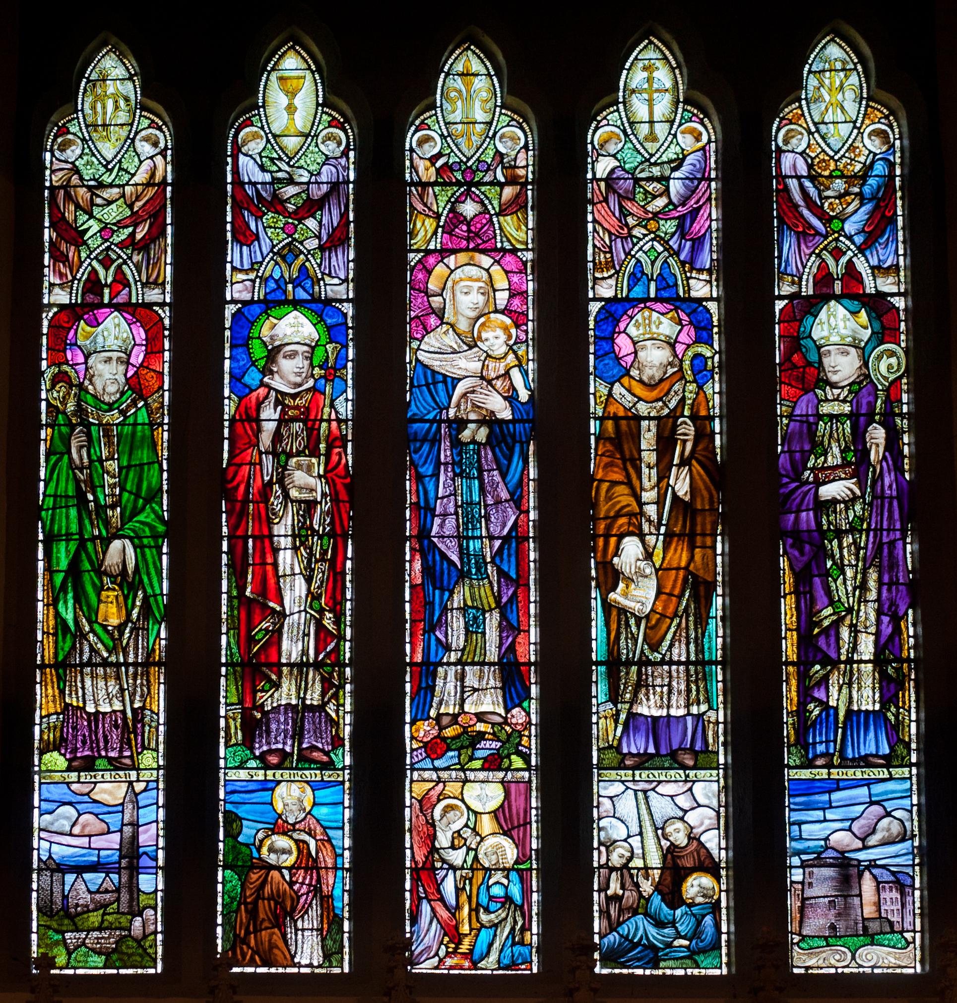 Glassmalerier bak alteret i kirken Our Lady and St Kieran i Ballylooby i grevskapet Tipperary, som avbilder fire lokale helgener sammen med Madonna og barnet. F.v. Declan av Ardmore, Kieran av Tubbrid (kirkens navnepatron), Maria med barnet, Carthagus av Lismore og Odran Maighistir