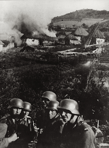 German soldiers after setting fire to a Serbian village, 1941.