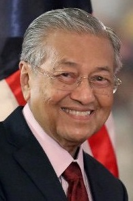 A smiling Mahathir stands in front of a Malaysian flag