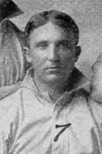 A man in a light baseball uniform.