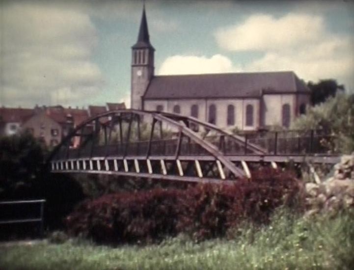 """Brücke über die Saar und den Saarkanal, verbindet die Orte Kleinblittersdorf und Grosbliederstroff, Verwendung des ehemaligen Saarbrücker """"Kummerstegs"""" von 1964 bis 1993, ab 1968 trägt sie den Namen """"Freundschaftsbrücke""""."""