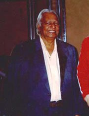 An old man in a blue suit and white shirt smiles at the viewer.