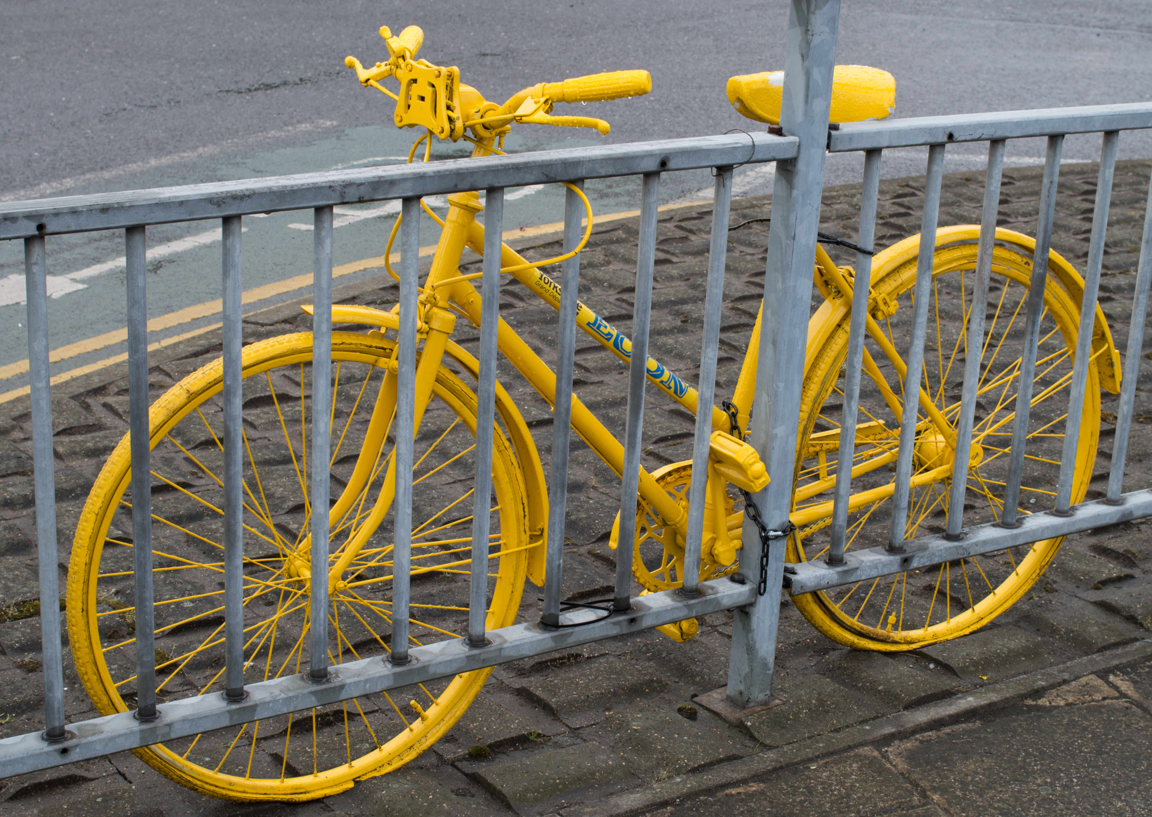 A bike painted yellow fastened to a railing