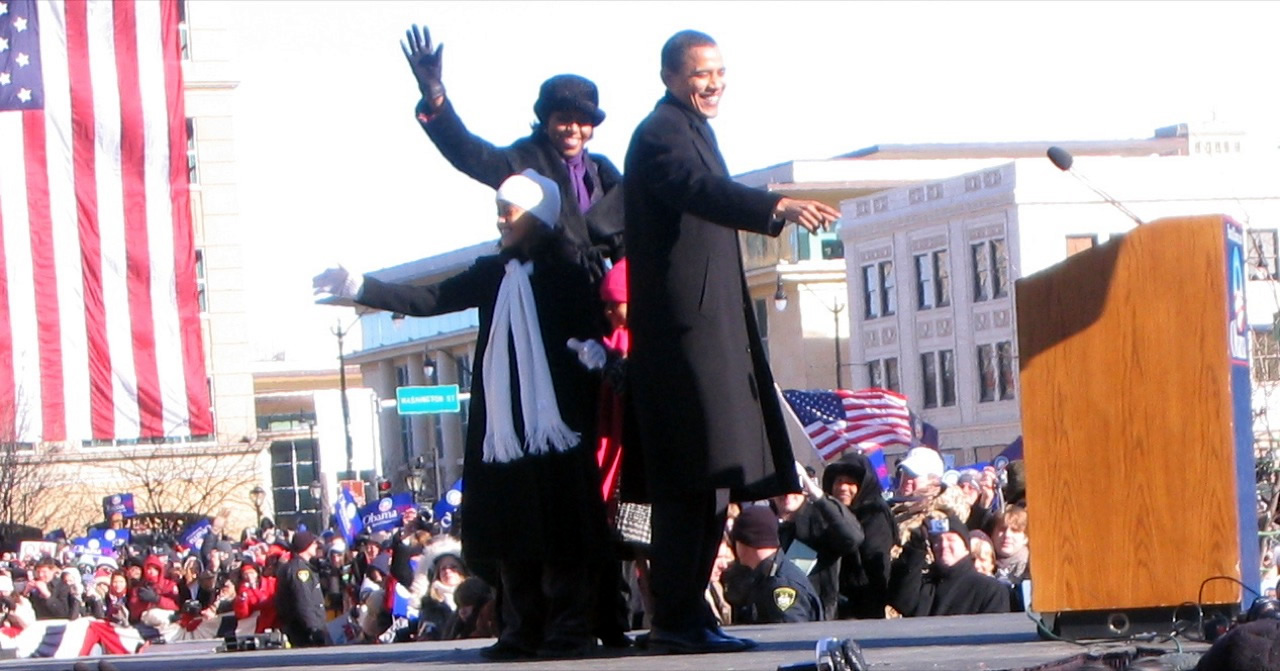 Obama stands on stage with his family. They wave.