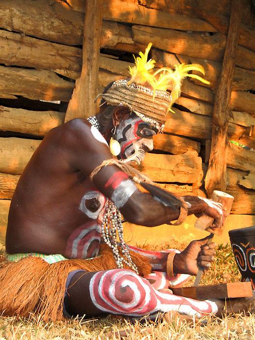 Seorang dari suku Asmat tengah membuat ukiran kayu
