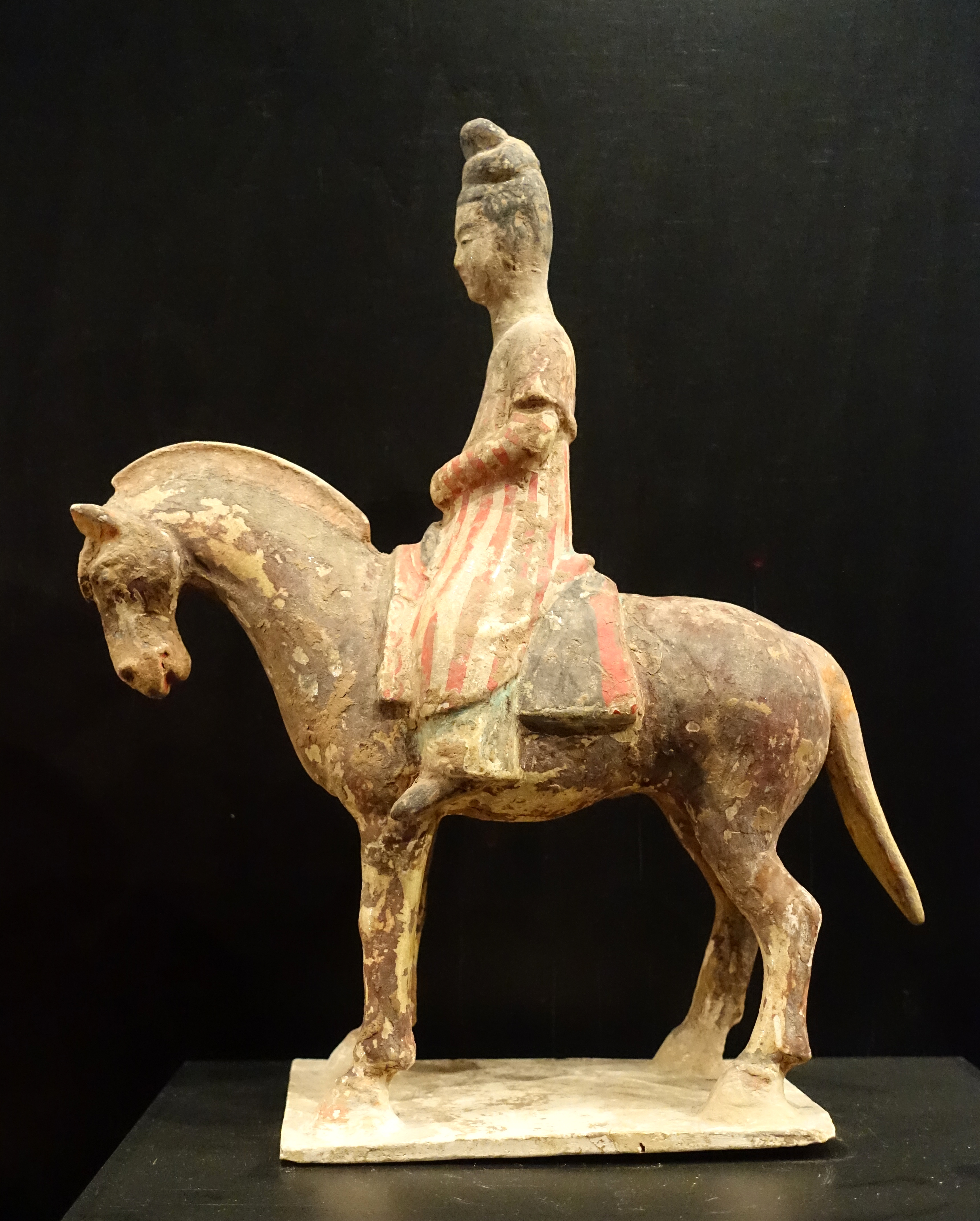 filetomb figurine of a woman riding a horse dressed in