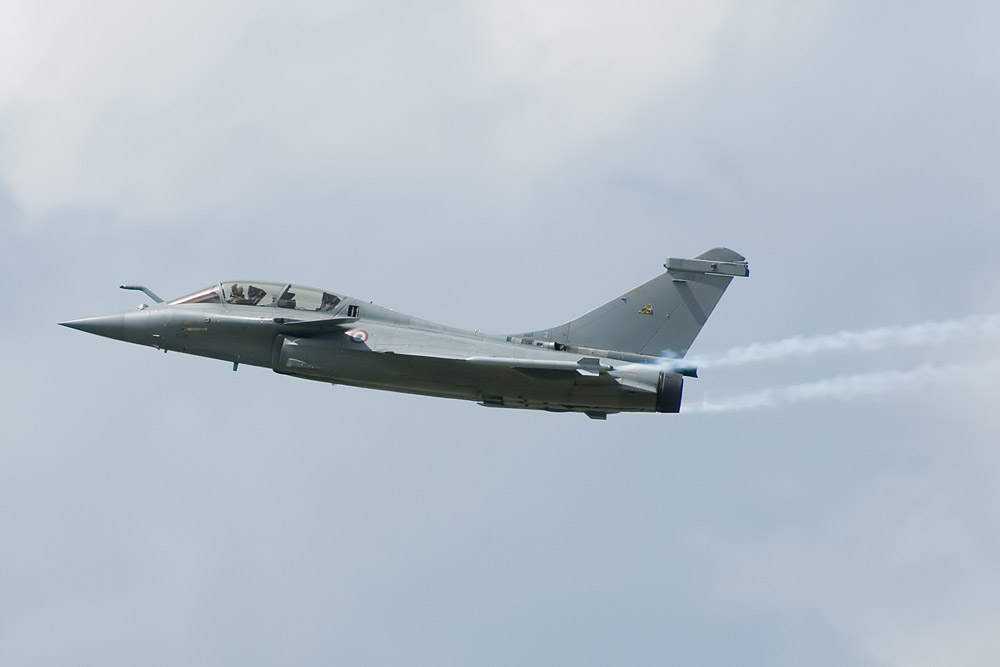 Pale gray jet aircraft flying towards left of camera. Smoke trial the aircraft's wing tips