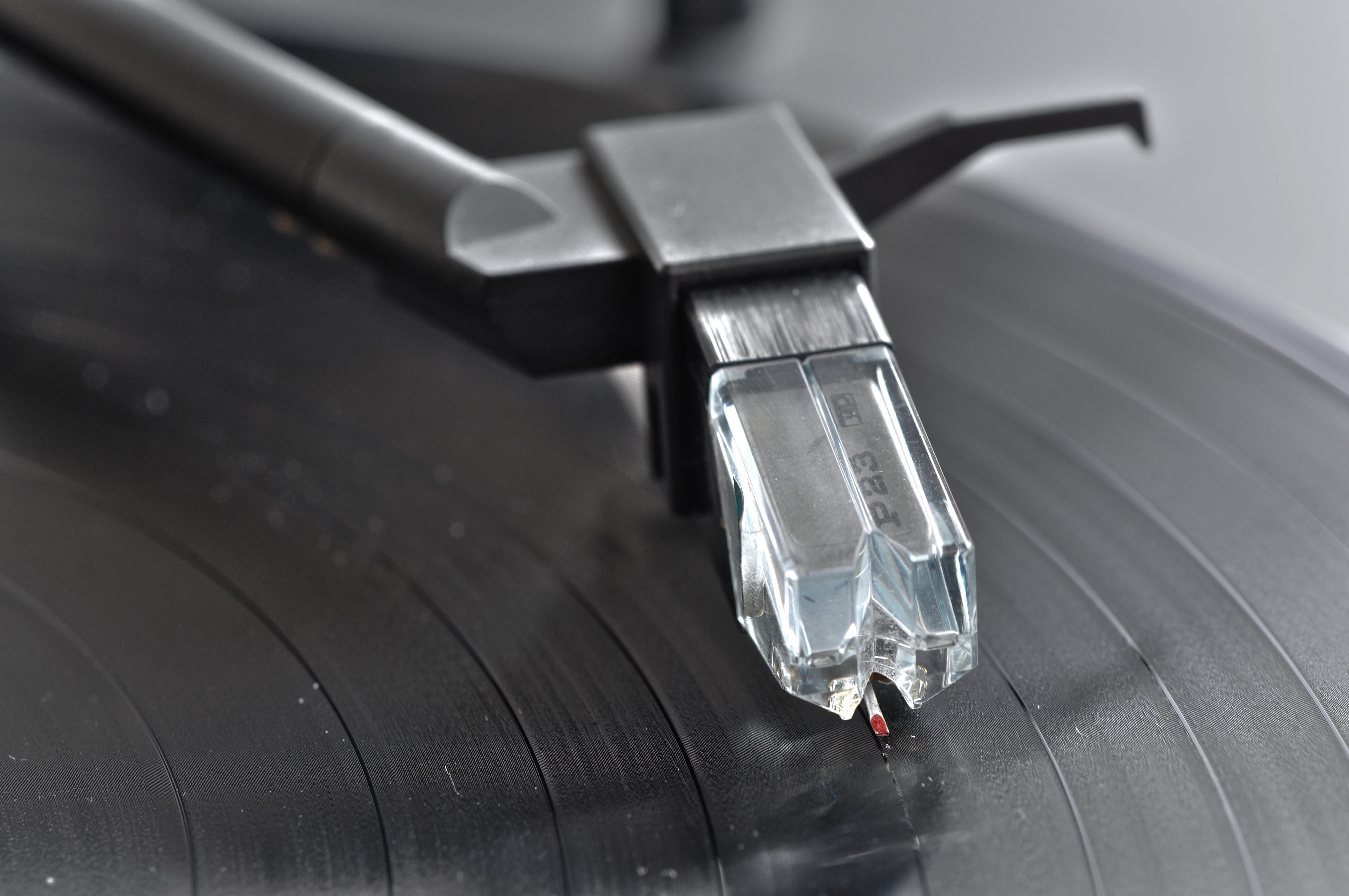 Tonabnehmer beim Abspielen einer Schallplatte; unter dem roten Lackpunkt befindet sich die Abtastnadel, deren Spitze in der Rille der Schallplatte läuft