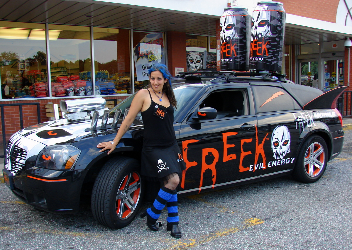 https://upload.wikimedia.org/wikipedia/commons/9/9b/Promotional_model_with_car_advertising_energy_drink.jpg
