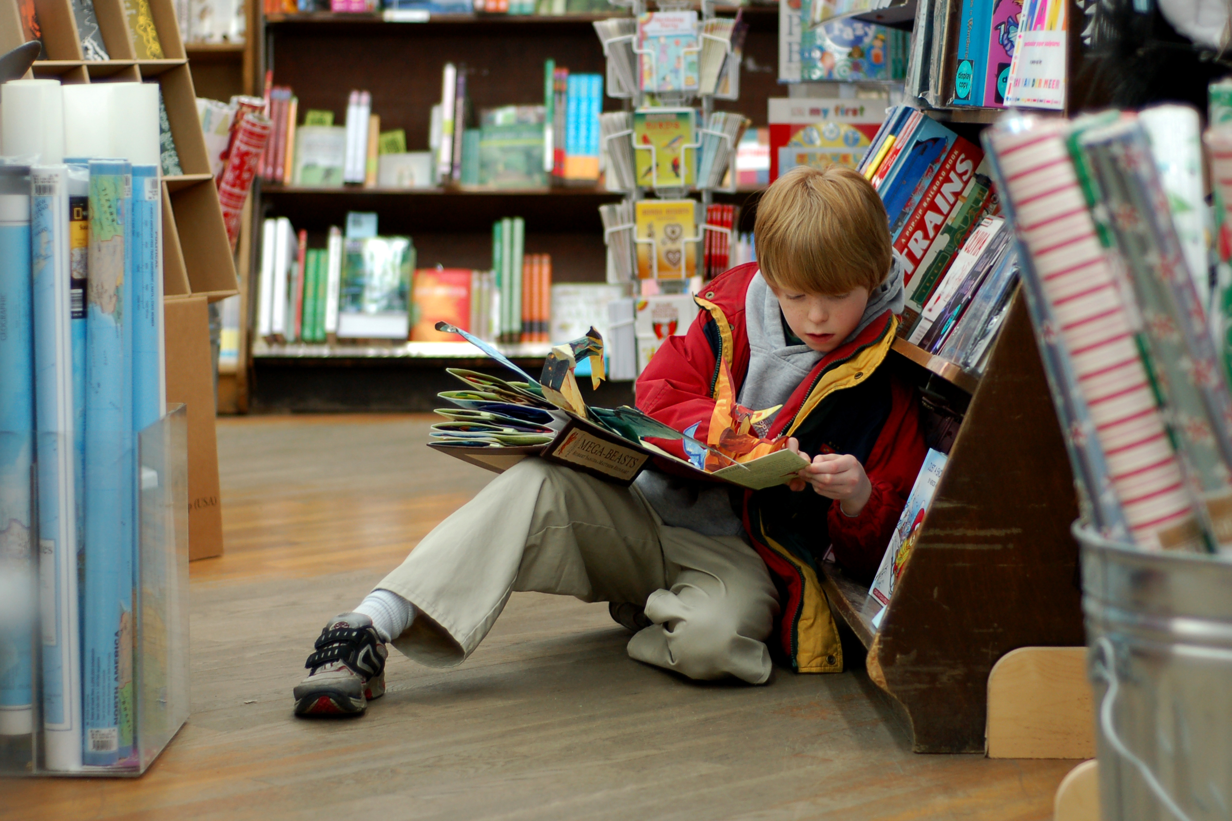 Boy reading book on the floor of a book store.