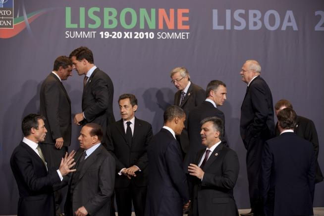 Twelve men in black suits stand talking in small groups under a backdrop with the words Lisbonne and Lisboa.
