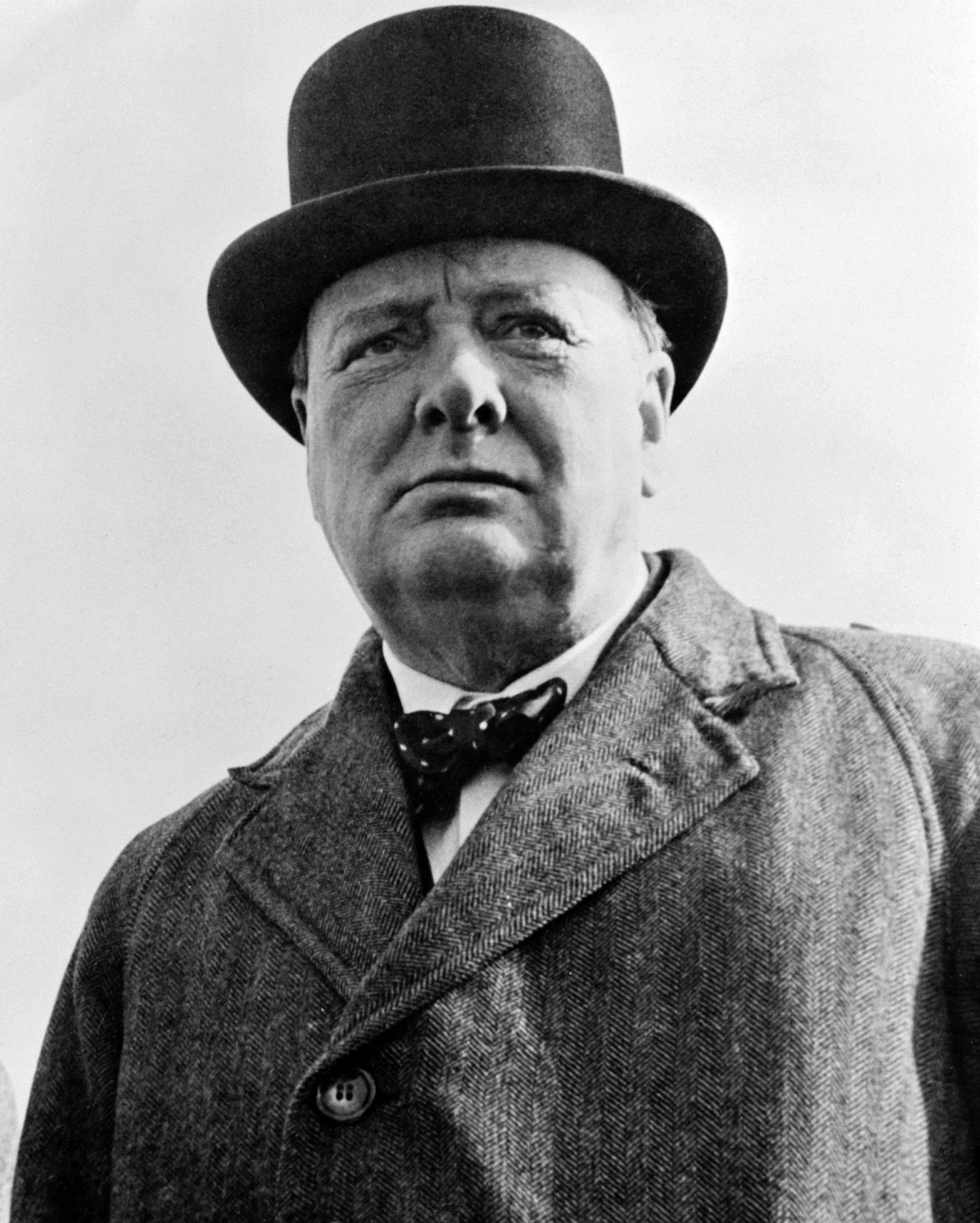 Photograph of Winston Churchill looking pensive while wearing an overcoat, tophat, and bowtie