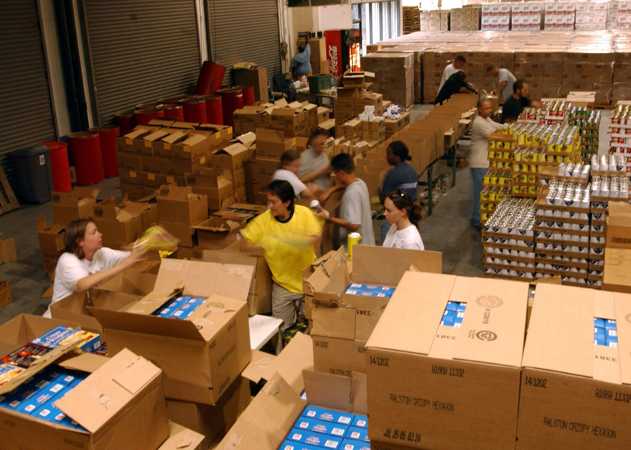 Men and women wearing yellow and white shirts  loading food into  cardboard boxes at a Food Bank