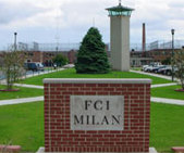 "A red brick sign in the foreground says ""FCI MILAN"". In the back, a solitary green tree is visible atop a grassy mound, with a tower to its right."