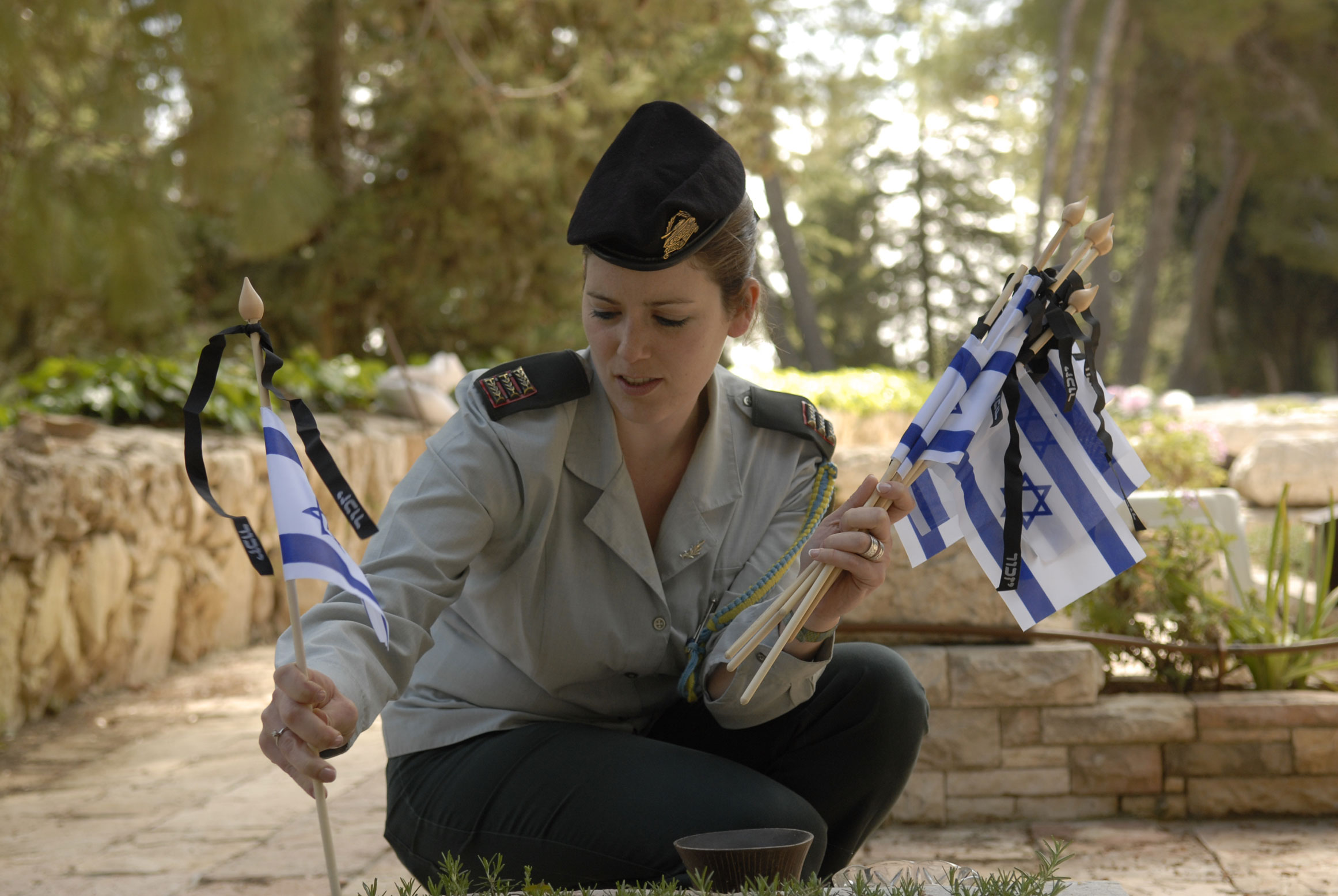 Israeli soldier plants flag at an Israeli soldier's grave